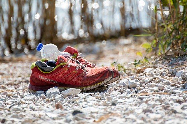 Et par røde Salomon løbesko med en tom vandflaske i den ene sko, der står på en grussti