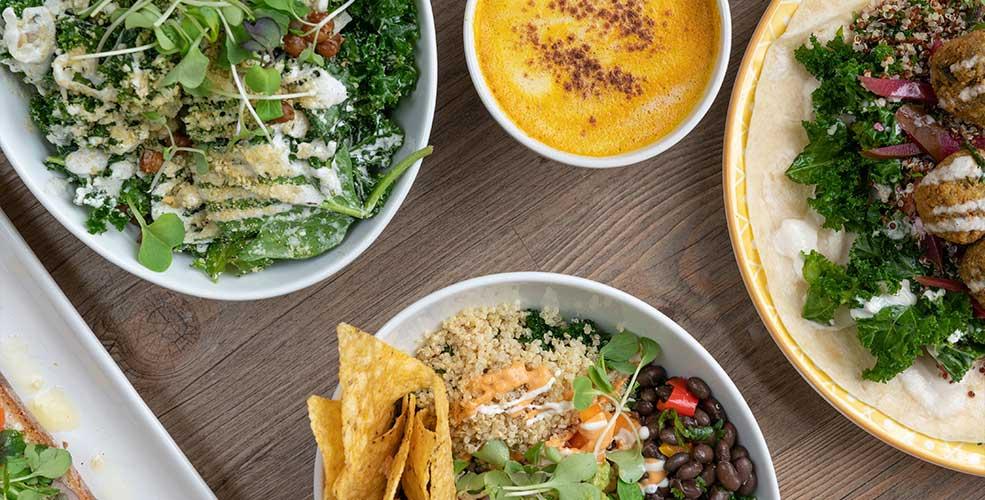 Træbord med fire skåle med forskellige salater