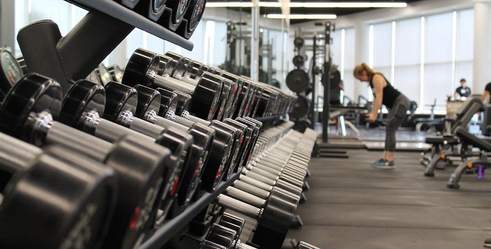Væg i fitnesscenter, hvor der er en masse forskellige håndvægte