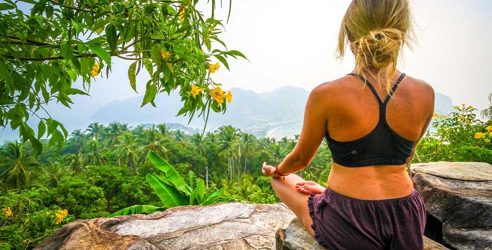 Kvinde der sidder på klippe og mediterer med udsigt til bjerge og træer