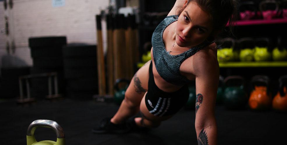 Kvinde i fitnesscenter der laver træningsøvelse, hvor hun ligger ned på en strakt arm med den anden arm løftet i lodret op.